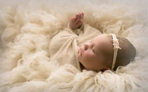 Newborn Girl Portrait. Angelic in Ivory Wrap on Flokati