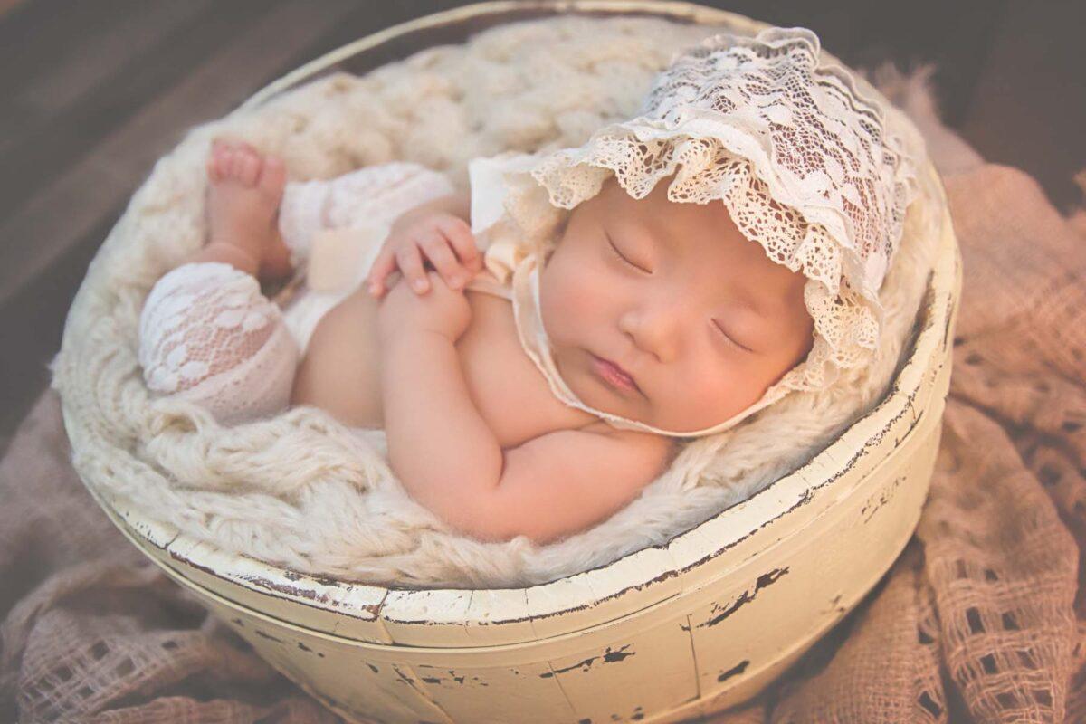 Adorable baby girl posed sleeping in wash basin